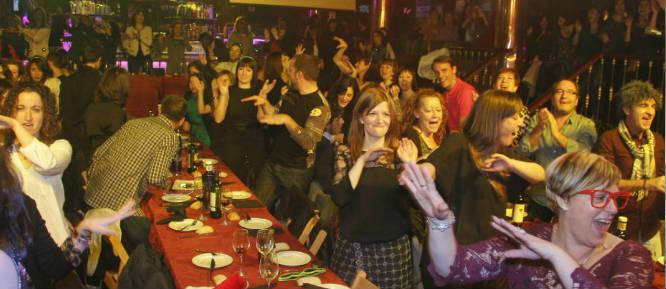 Grupos de amigas y amigos en cena espectáculo en Madrid